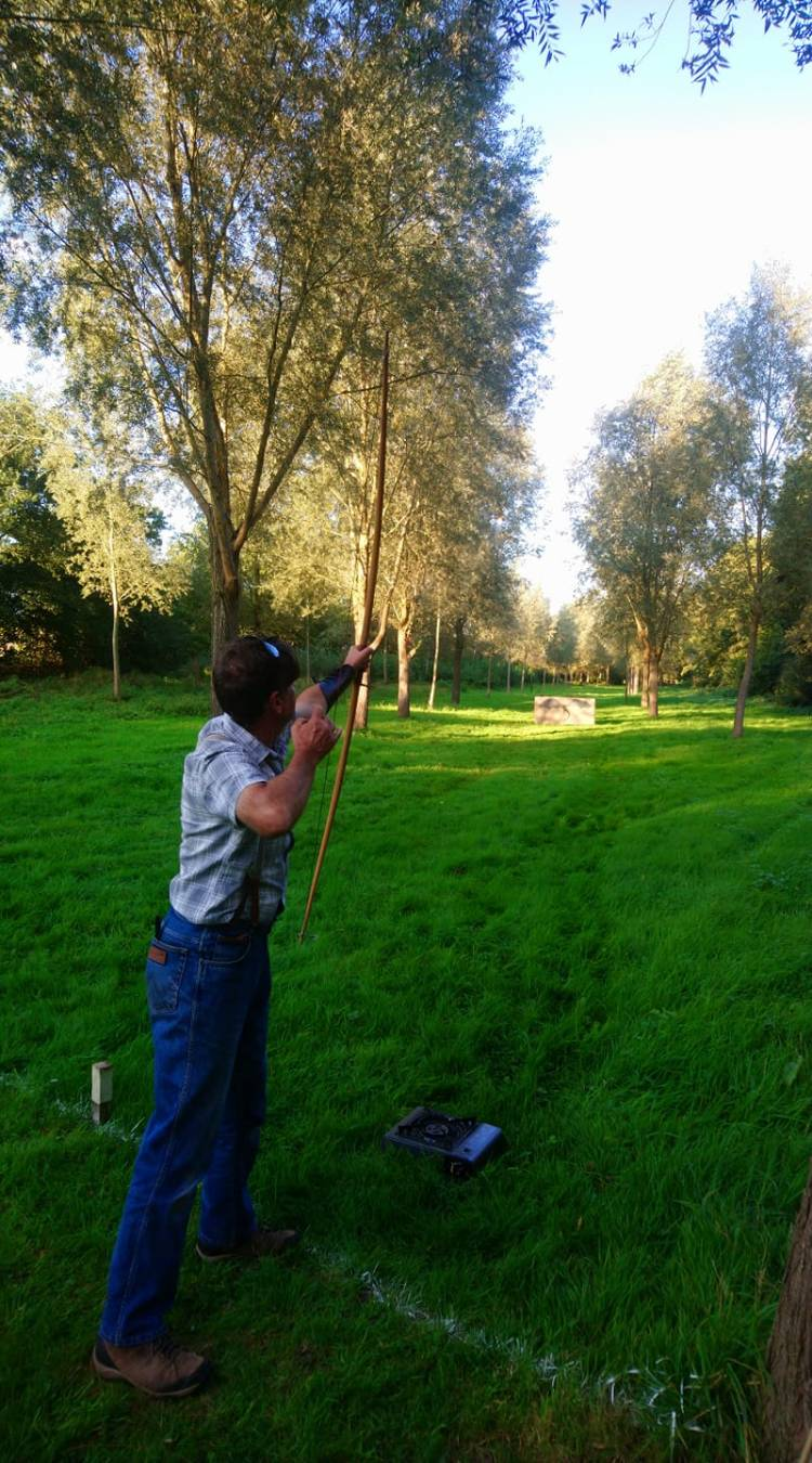 Man shoots an arrow into the air from a longbow on a long-distance clout archery range