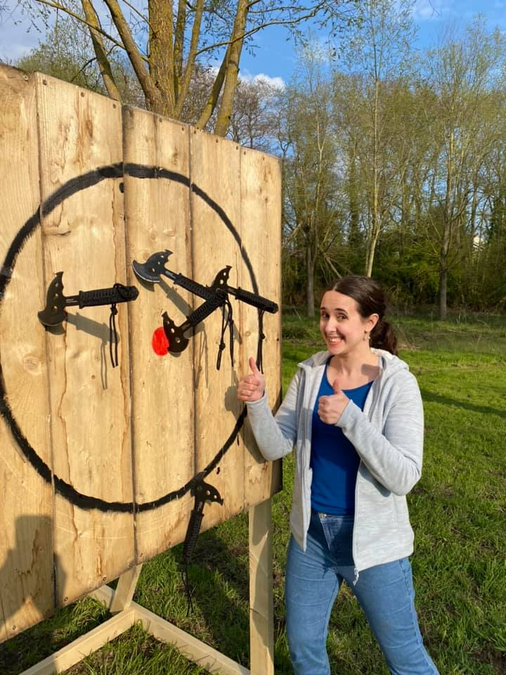Grinning woman with four throwing axes in target