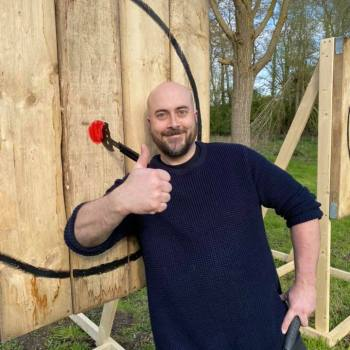 Happy man with axe that he has thrown into the bullseye of a target