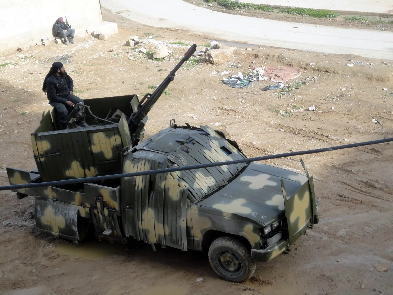 This technical is built from a pickup truck chassis and mounts a large anti-aircraft gun. It also features improvised armor and camouflage.