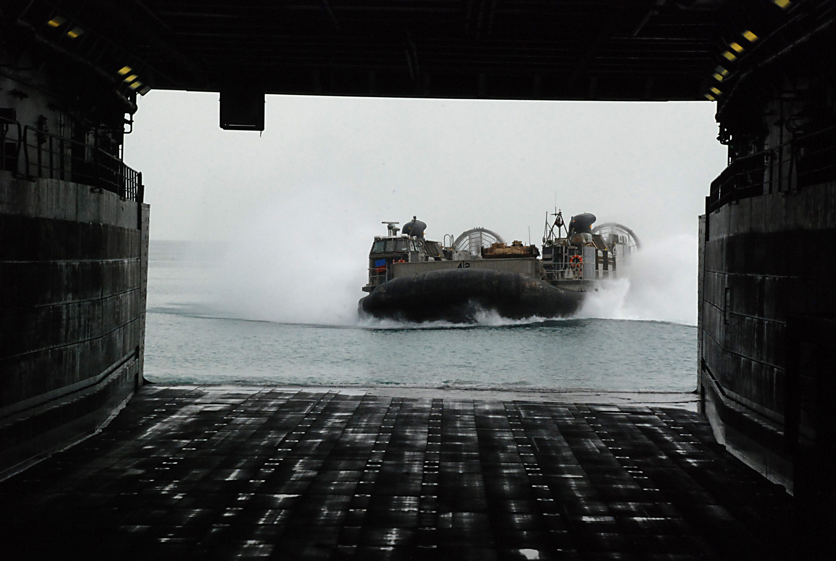 "A Landing Craft Air Cushion (LCAC) approaches the well deck of the amphibious transport dock ""USS Green Bay."""