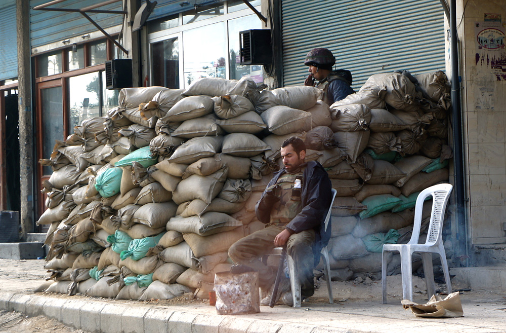 Syrian Arab Army soldiers smoke cigarettes while manning a checkpoint in Damascus. Photo: Elizabeth Arrot.