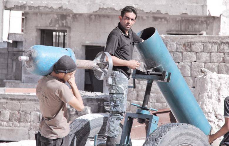 Fighters load a hell cannon with its propane tank projectile.