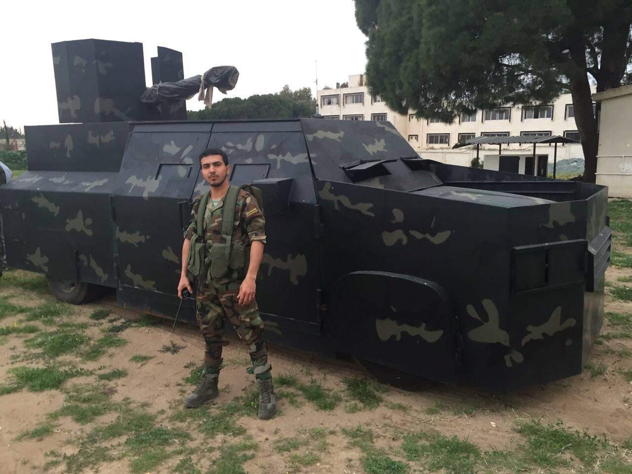 A Syrian fighter stands near an improvised armored personnel carrier.