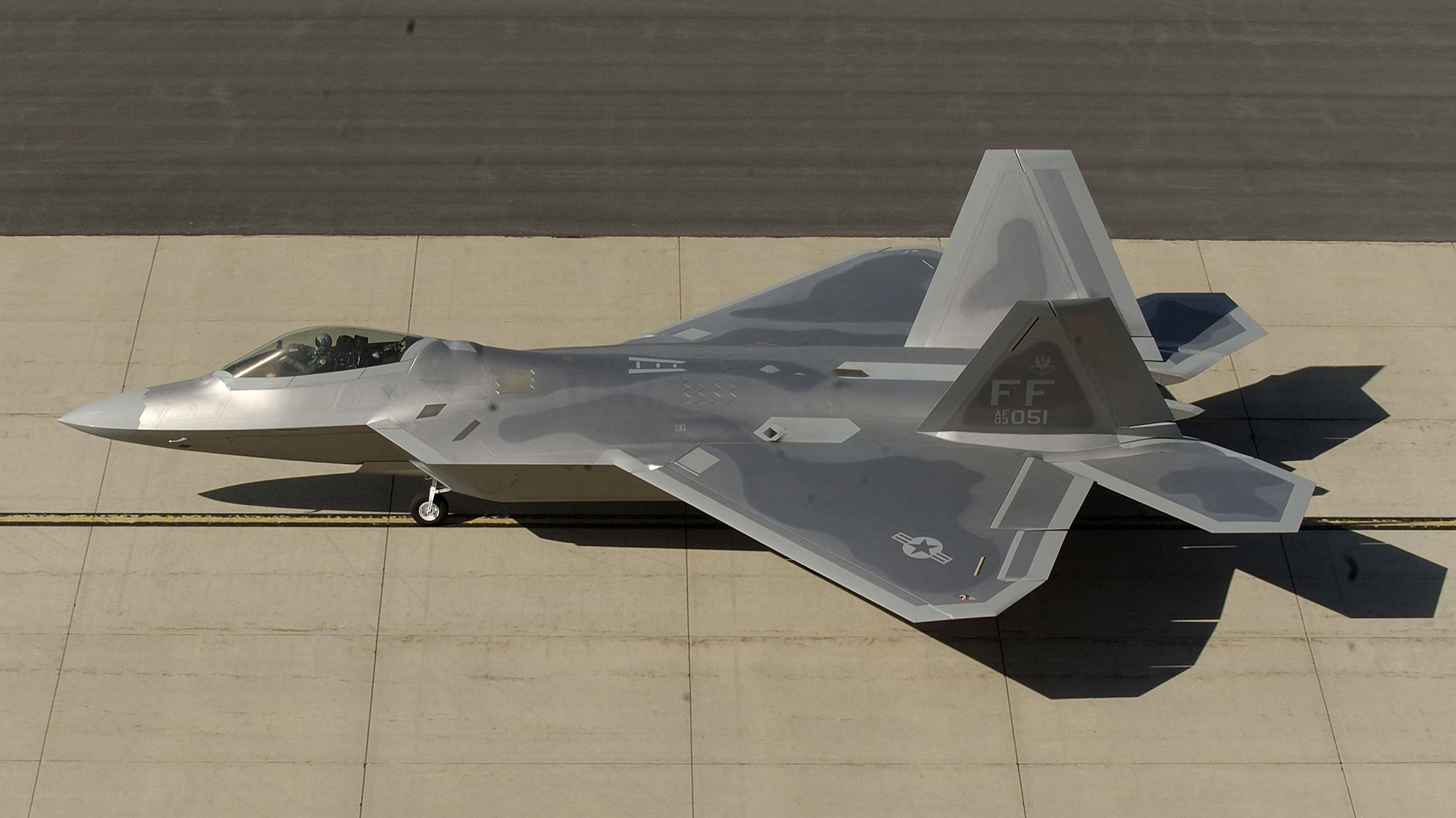 An F-22 taxis on a runway during an exercise.