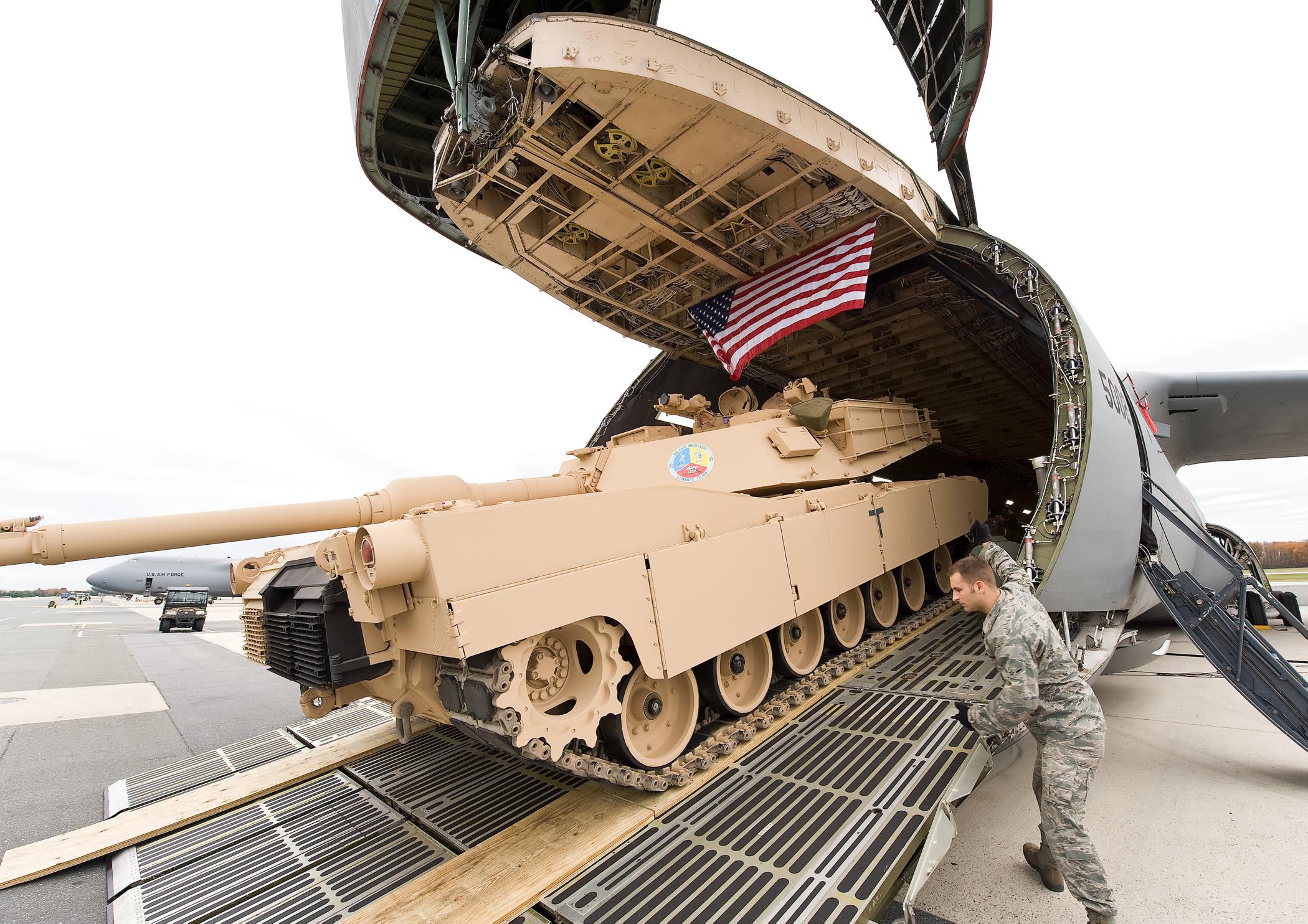 Airmen load a M1A1 tank onto a C5M Super Galaxy airlifter.