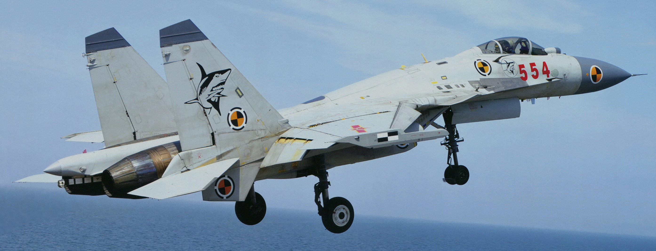 A J-15 aircraft during takeoff. This aircraft has a more combat-ready grey livery but still sports the calibration markings seen on the yellow J-15.