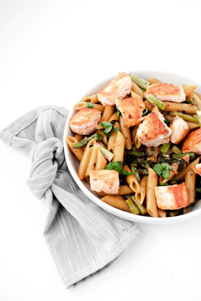 salmon penne pasta in white bowl with a napkin