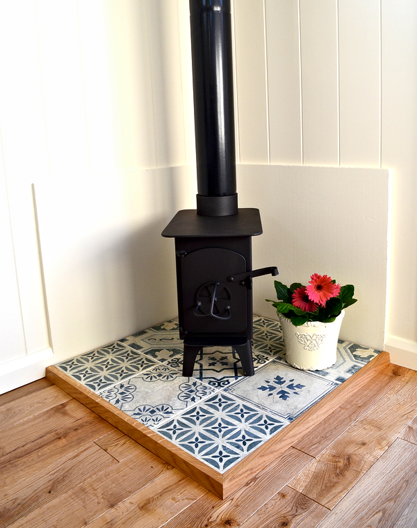 little wood burning stove with blue tiled hearth