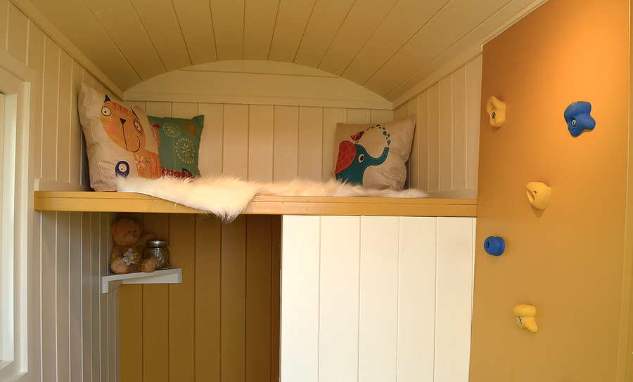 Inside a children's Hutlet with mezzanine platform and climbing wall access