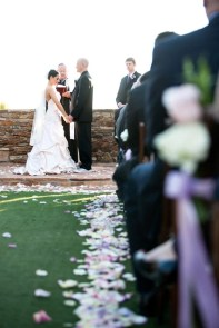 An aisle in an outdoor wedding lined with rose petals