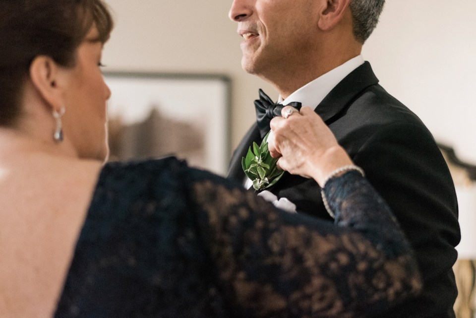 Mother of the groom fixing her husbands boutonniere