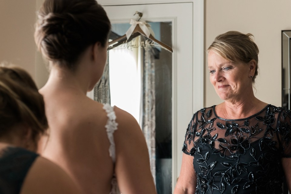 Mother of the bride smiling proudly at her daughter as she puts on her wedding dress at the Palmer House in Chicago IL