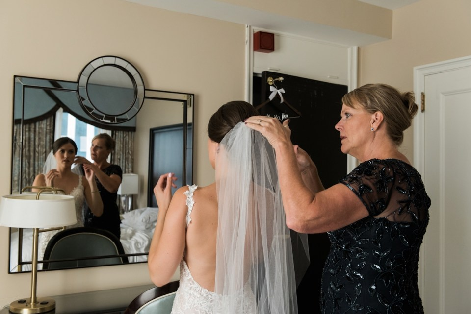 Mom helping her daughter put on her wedding veil at the Palmer House in Chicago IL