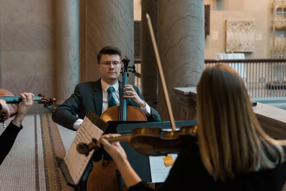 Small string quartet playing for wedding guests at the Art Institute of Chicago Grand Staircase