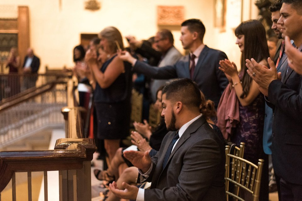 Wedding guests applaud for the newlyweds
