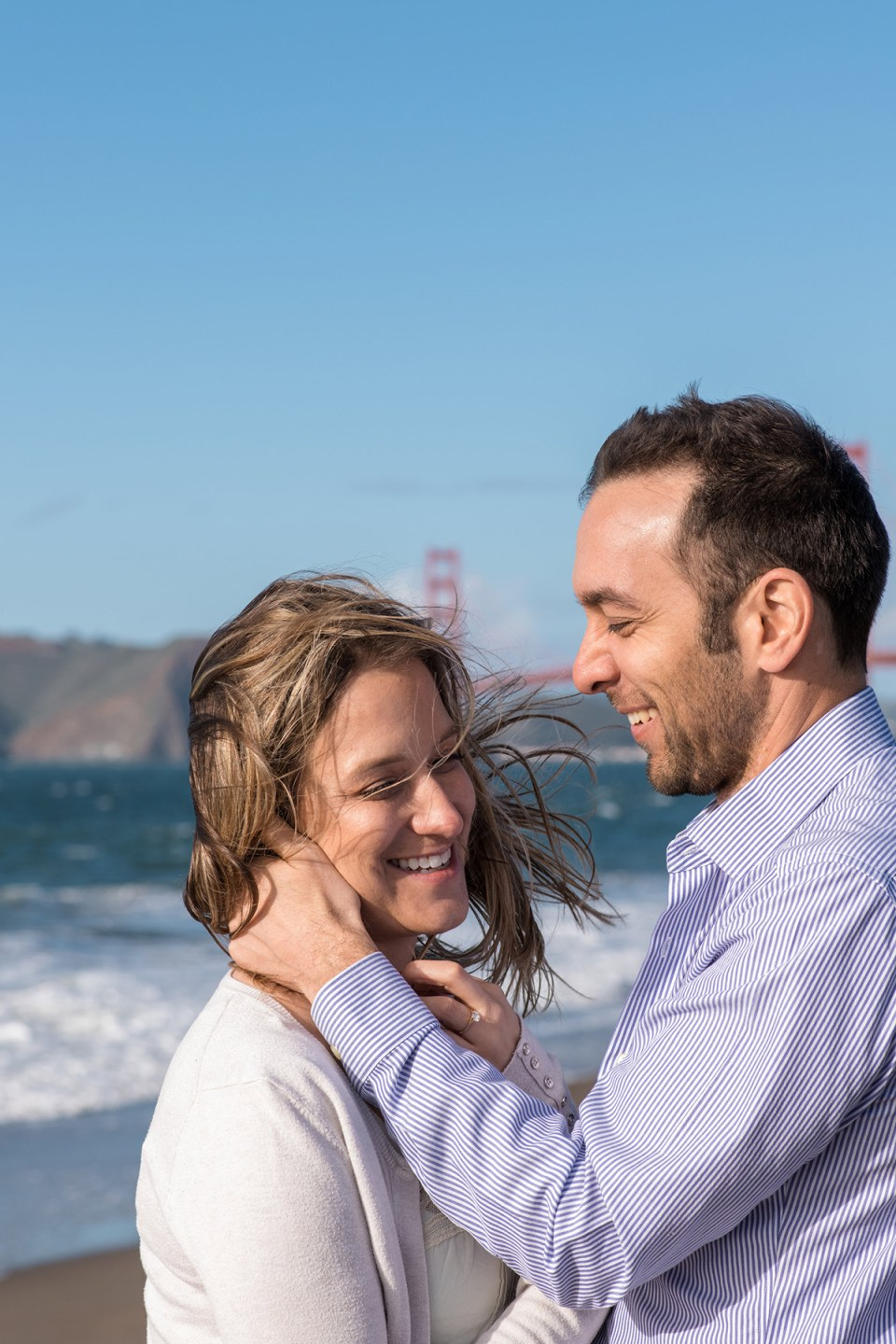 Couple laughing on a windy day at Baker Beach in San Francisco