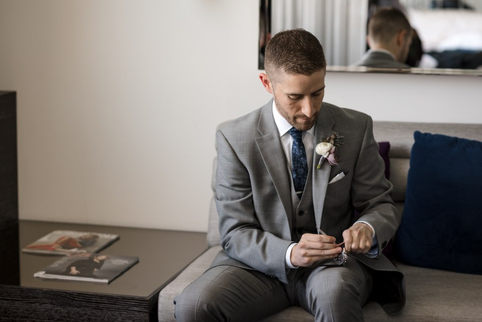 Groom opening a gift from the Bride on his wedding day at the W Hotel Lakeshore in Chicago IL