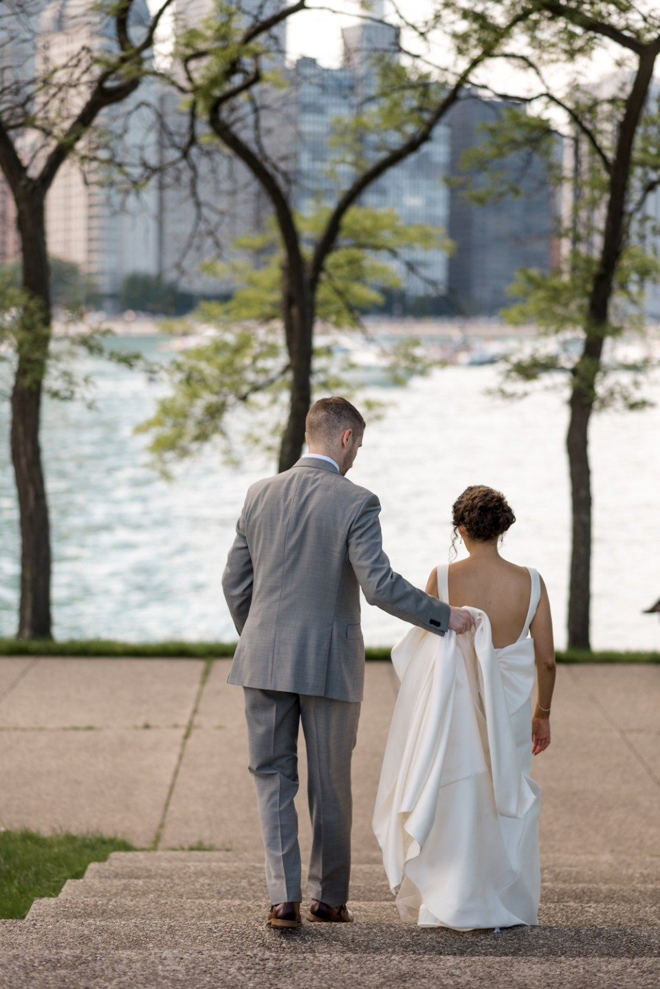 Groom helps hold Bride's dress during portraits at Olive Park in Chicago IL