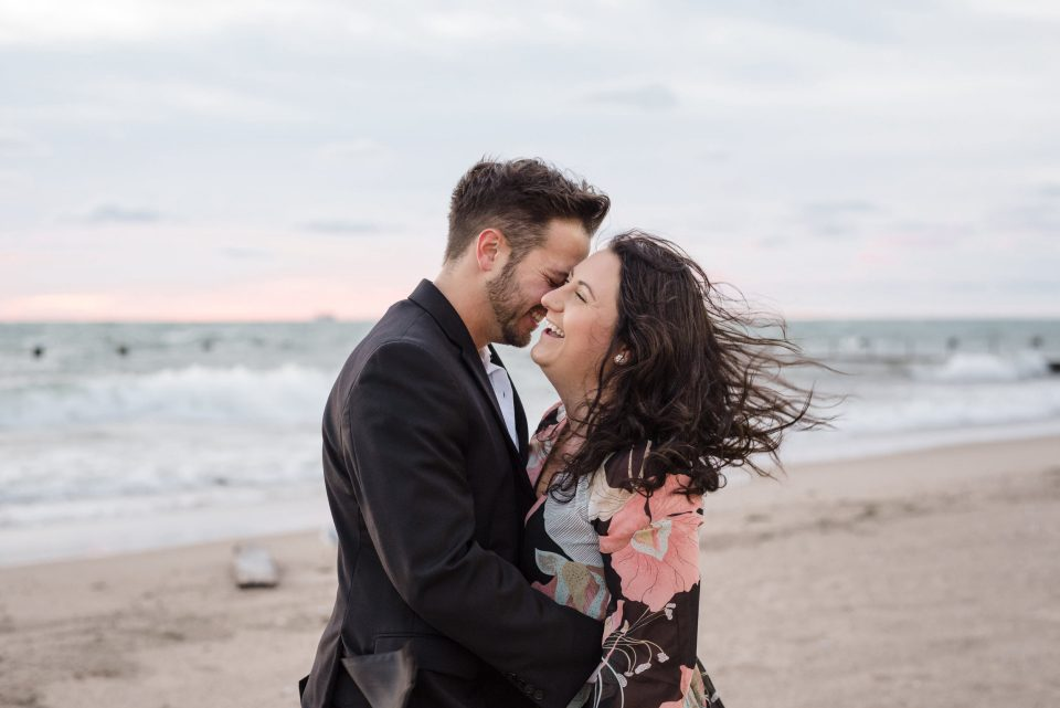 Young couple laughing on North Avenue Beach in Chicago Illinois
