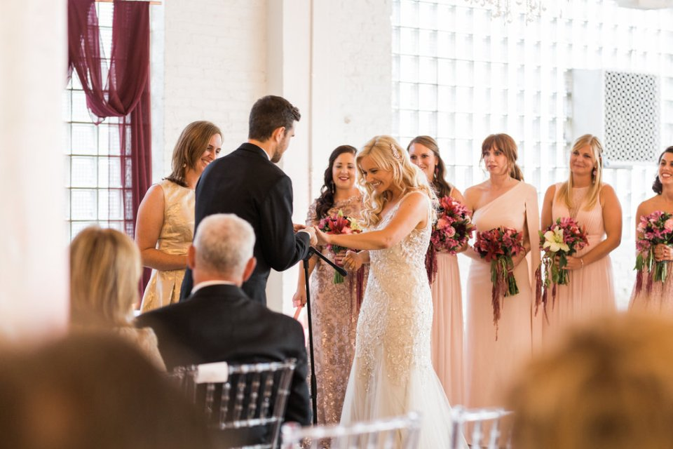 Groom putting on the bride's ring at Room 1520 in Chicago IL