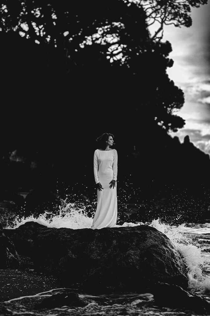 A young woman wearing a bridal gown stands on a rock at Mount Maunganui beach