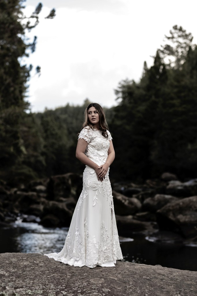A woman in a white wedding gown stands on a rock near water at McLaren Falls near Tauranga