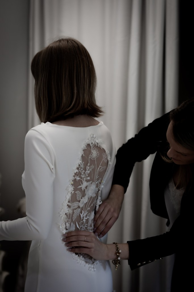A bridal gown designer in Tauranga makes an adjustment to a wedding dress worn by a young woman