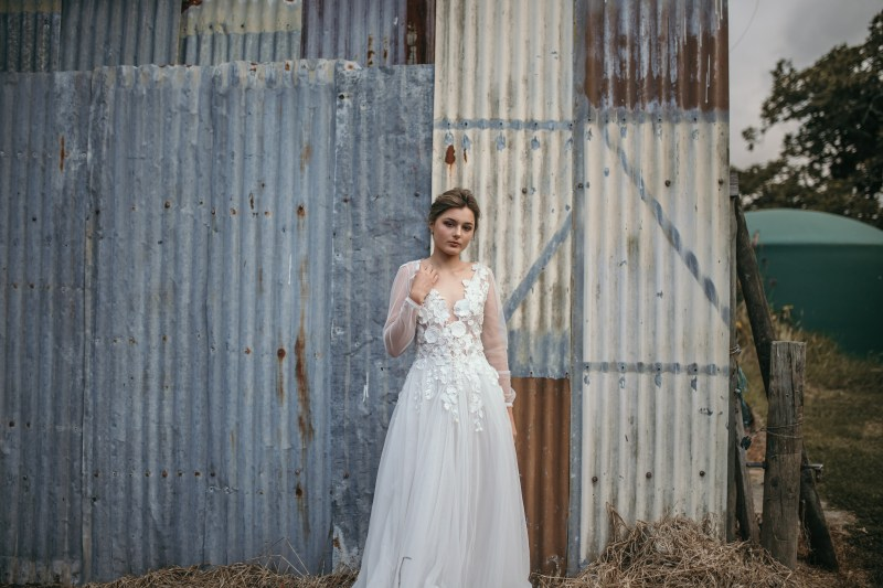 A woman in a bridal gown stands in front of shed in a field