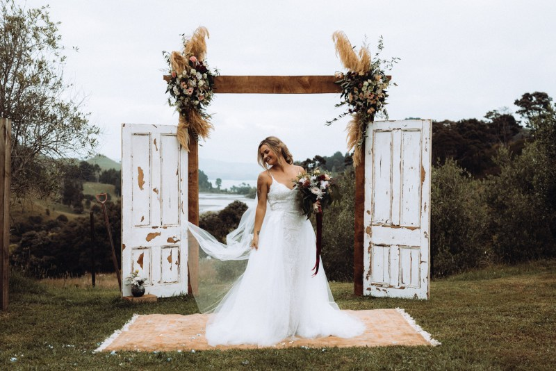 A bride stands at the altar in a gown by White Silk Bridal of Tauranga