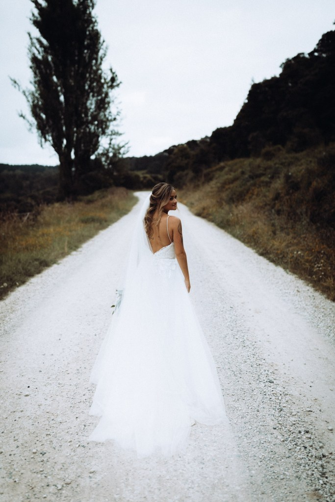 A woman in a wedding gown stands in the middle of a rural road