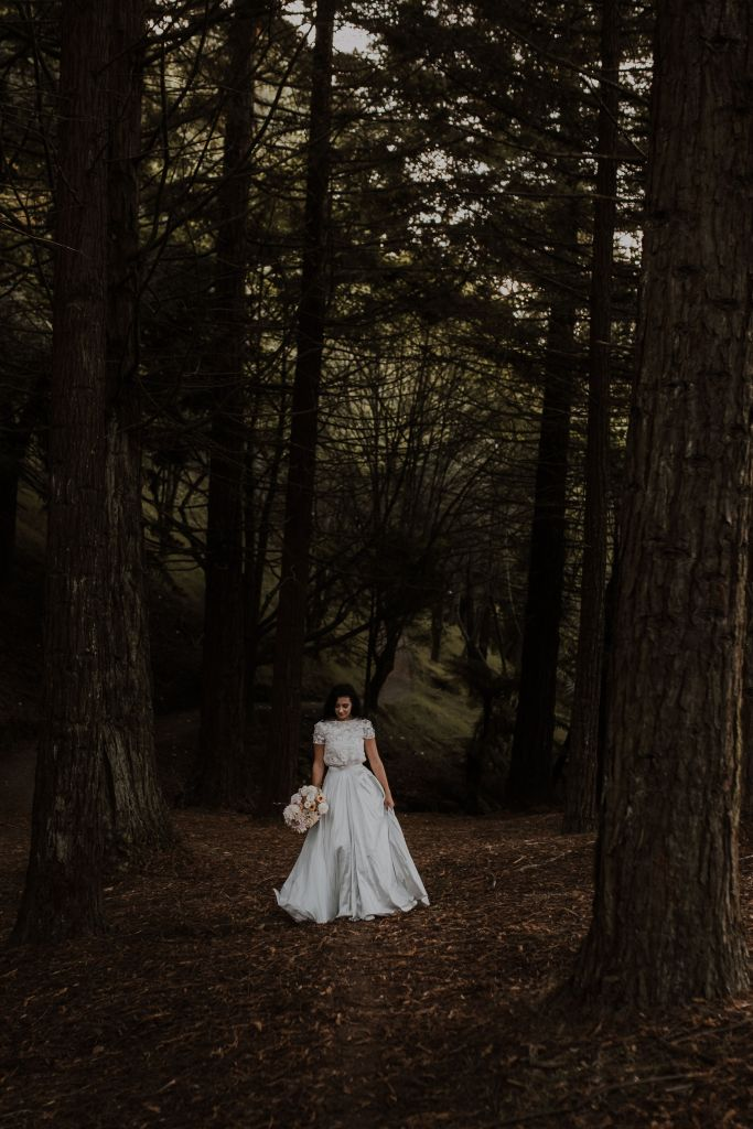 A woman walks through a forest wearing a wedding gown by White Silk Bridal of Tauranga