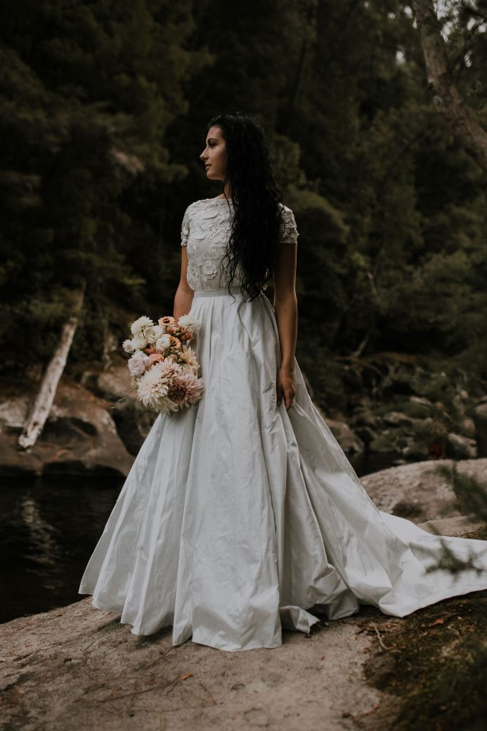 A woman with dark hair and wearing a bridal gown stands on a rock on the side of a river