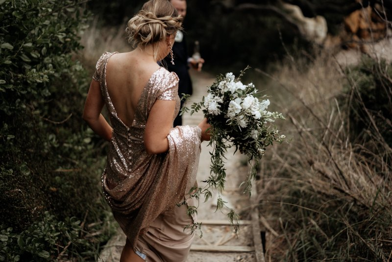 A woman in a sparkly wedding gown walks down outside steps