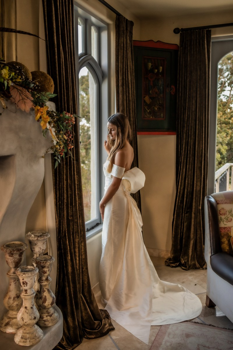 A woman in a bridal gown looks outside a big window in a house near Tauranga