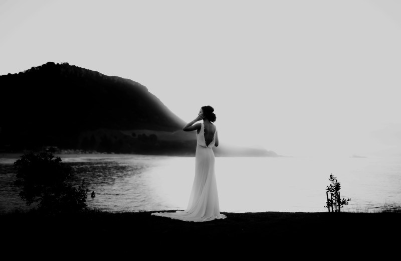 A woman in a white wedding dress stands on a rock near Mount Maunganui beach