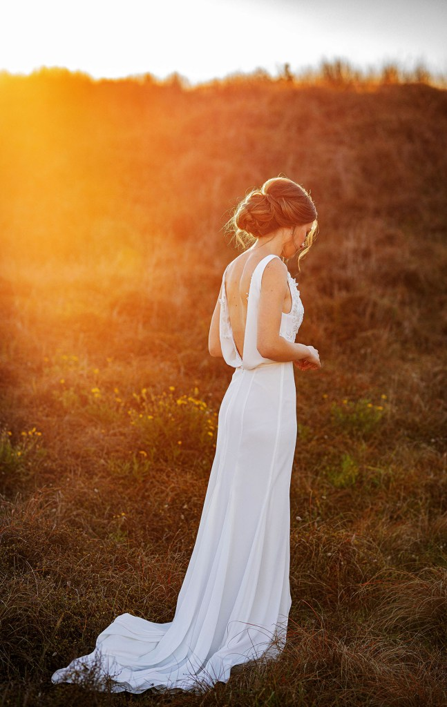 A woman wears a bridal gown whilst standing in sand dunes in Tauranga