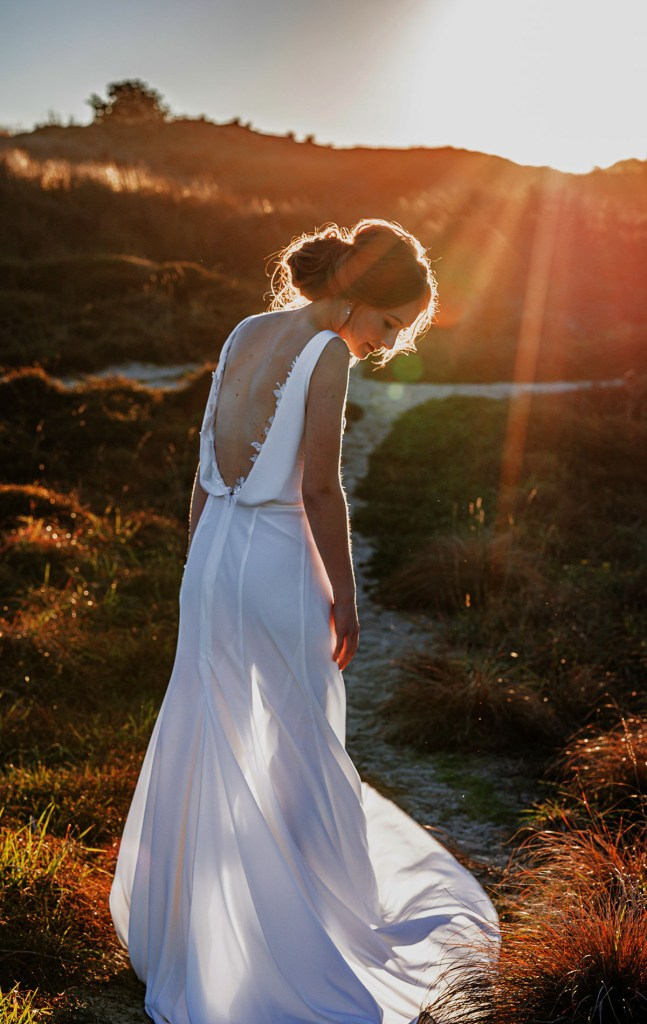A woman wearing a white bridal gown looks down whilst she stands in sand dunes near Tauranga