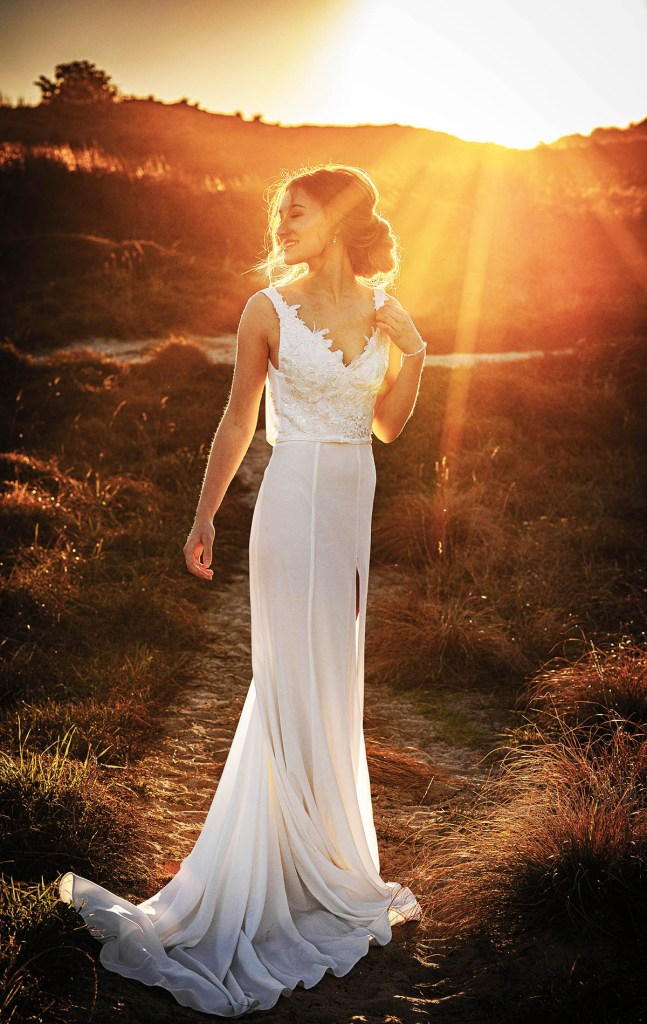 A woman in a white bridal gown smiles as she stands in sand dunes in Tauranga