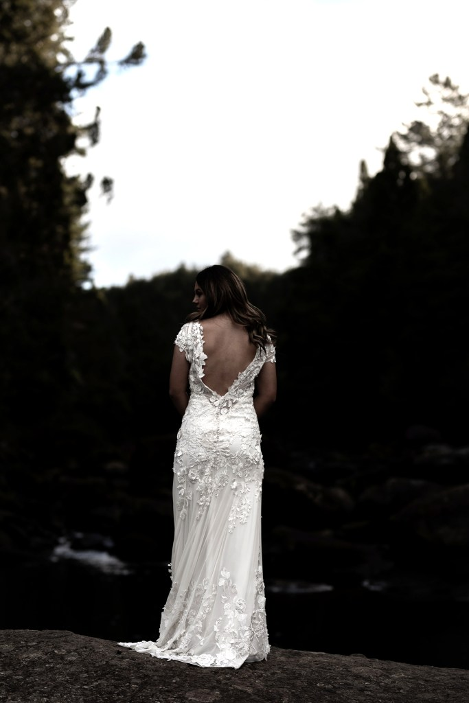 A woman wearing one of the designer bridal gowns by White Silk Bridal in Tauranga stands on a rock