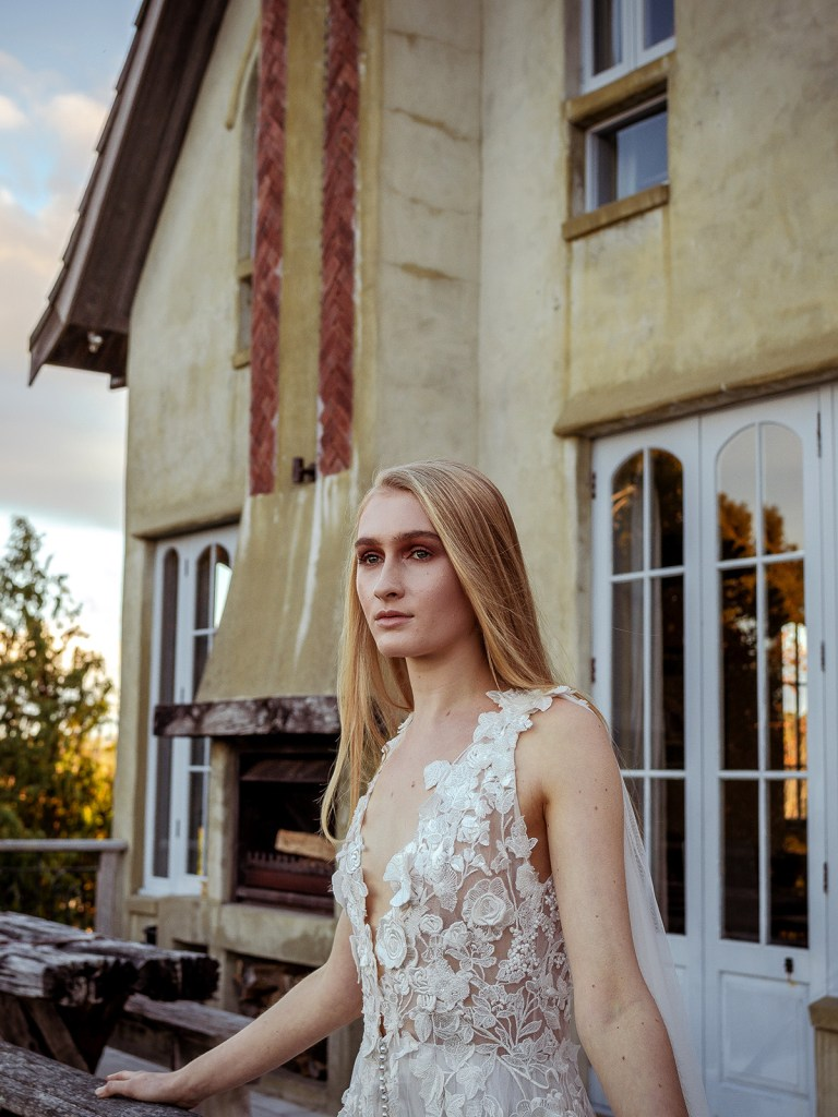 A woman looks out as she wears one of the designer bridal gowns by White Silk Bridal in Tauranga