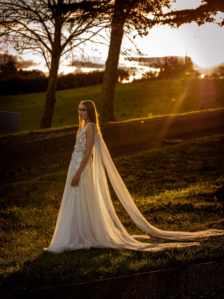 A woman stands on a Tauranga farm whilst wearing one of the designer bridal gowns by White SIlk Bridal