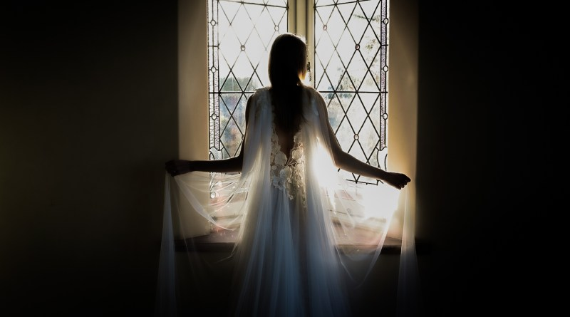 A woman wearing a designer wedding dress stands in front of a window in a house near Tauranga