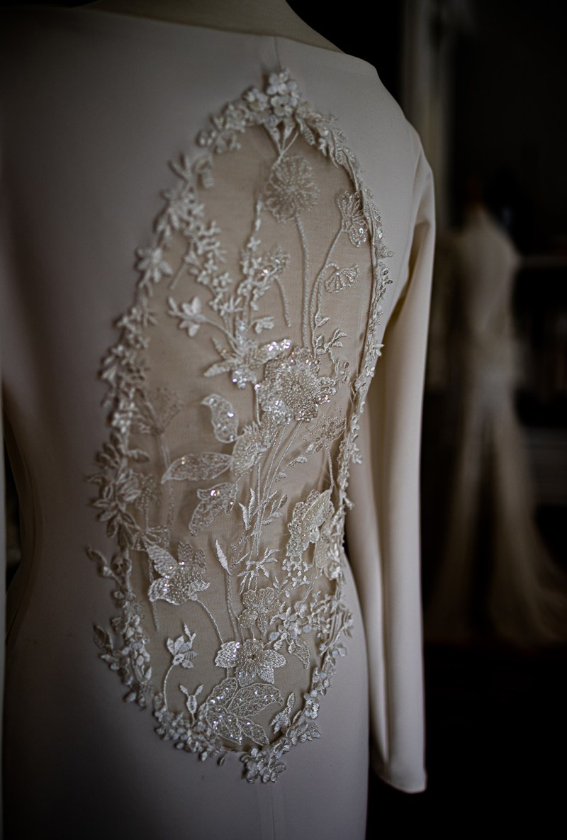 A wedding dress with intricate detail seen from the back in White Silk Bridal Couture's boutique