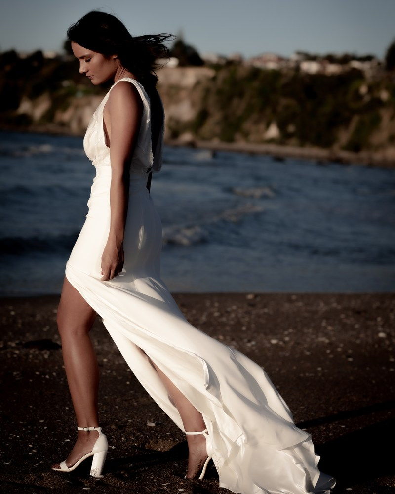 A woman stands in a white wedding dress on a beach