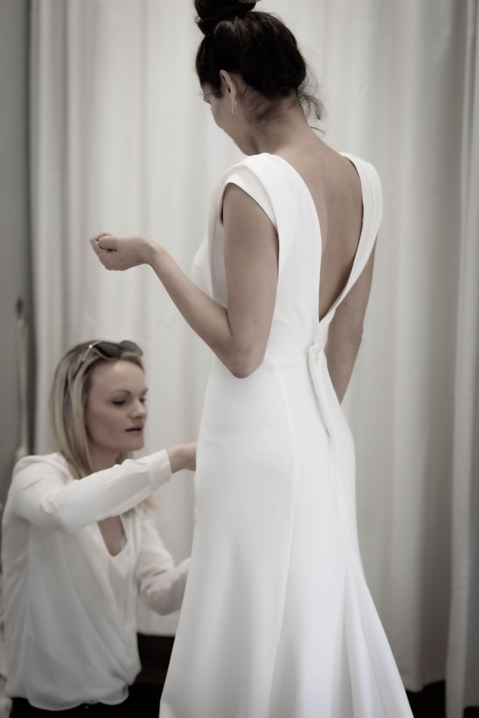 A bridal gown designer makes alterations to a wedding dress worn by a woman