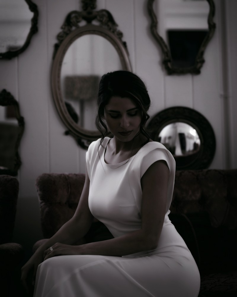 A woman in a white wedding dress sits on a chair with mirrors behind her