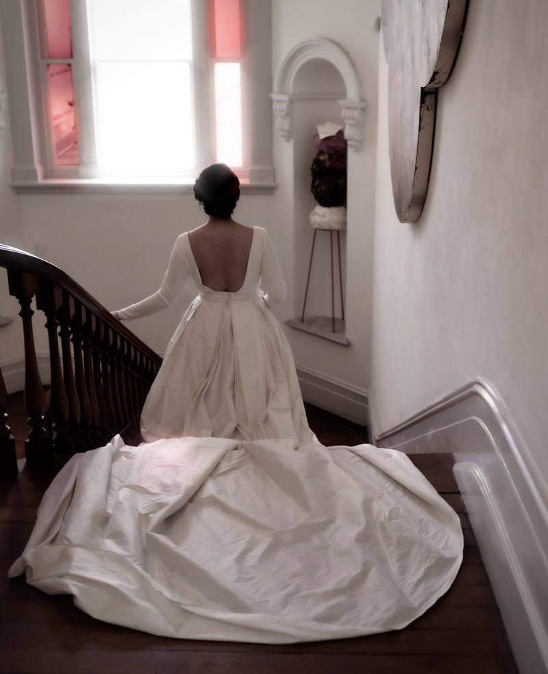 A woman in a bridal gown walks down long wooden stairs