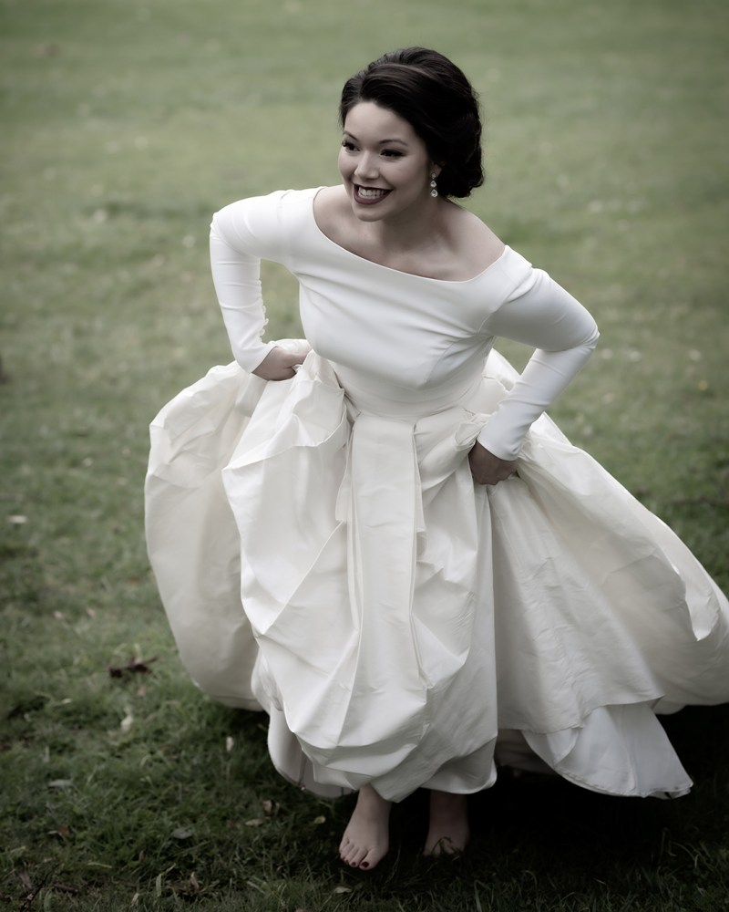 A woman in a white bridal gown walks on the grass
