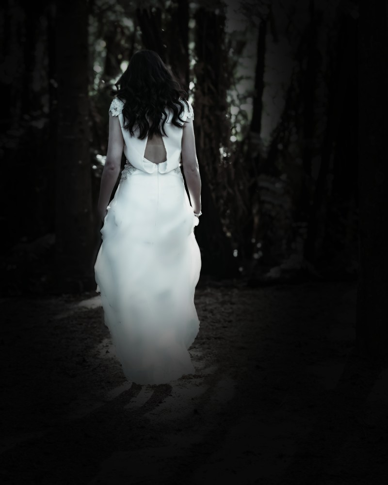 A woman walks through a wood whilst wearing a white bridal gown